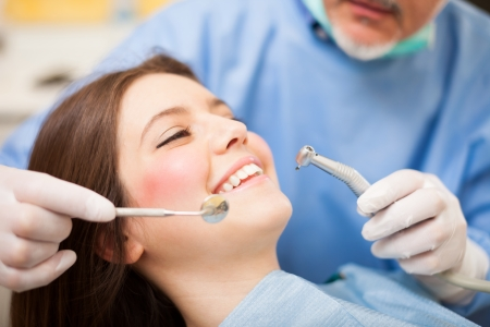 dental mirror: Dentist doing a dental treatment on a female patient