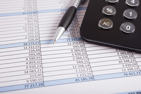 spreadsheets: Calculator and pen over a business document Stock Photo