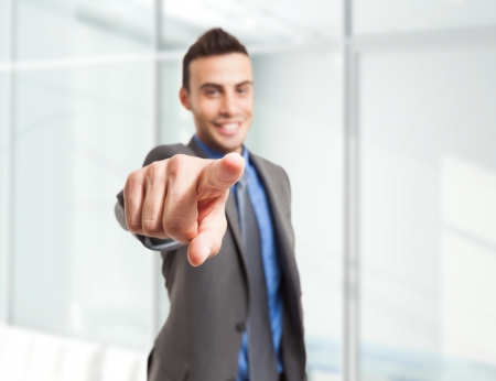 Smiling businessman pointing his finger to you photo