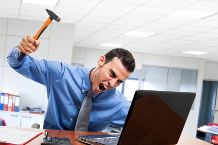 broken computer: Angry man smashing his laptop