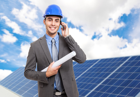 Smiling engineer in front of solar panels photo