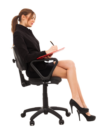 Woman taking notes while sitting on a chair photo