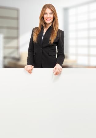 Beautiful woman showing a white board photo