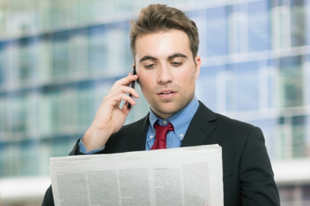 Young man talking on the phone while reading the newspaper photo