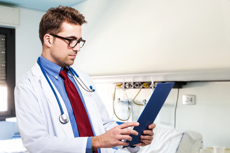 Doctor reading a case history photo