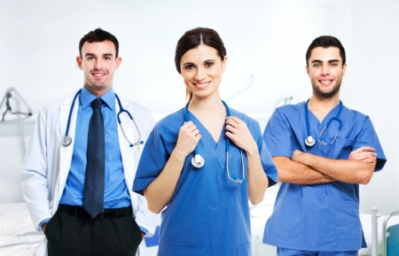 nursing staff: Portrait of a smiling nurse in front of her medical team Stock Photo
