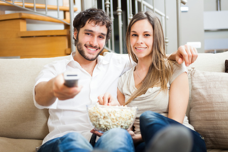 tv remote: Young couple preparing to watch a movie