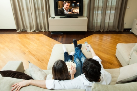 Young couple eating popcorn while watching a movie Stock Photo - 22770610