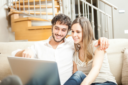 Couple using a notebook while relaxing on the couch Stock Photo - 22770614