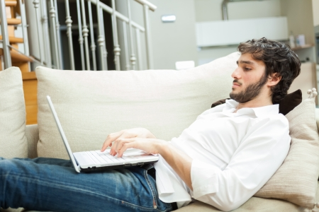 Man using a laptop while relaxing on the couch Stock Photo - 22770615