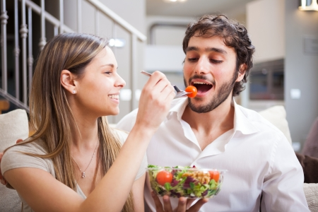 eating in: Couple eating a salad in the living room Stock Photo