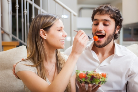 Couple eating a salad in the living room photo