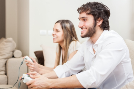 Young couple playing video games in their apartment Stock Photo - 22770713