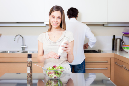 Woman cooking spicing a salad in her kitchen photo