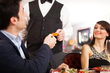 pagando: Hombre que paga la cena en un restaurante Foto de archivo
