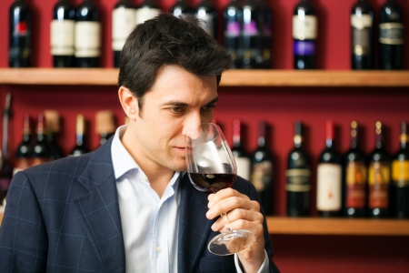 赤ワインのグラスを試飲するソムリエ