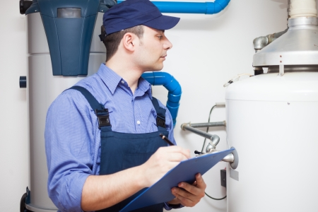 plumbing: Technician servicing an hot-water heater