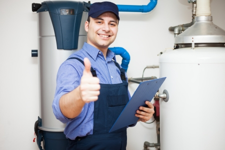 Smiling technician servicing a hot-water heater photo