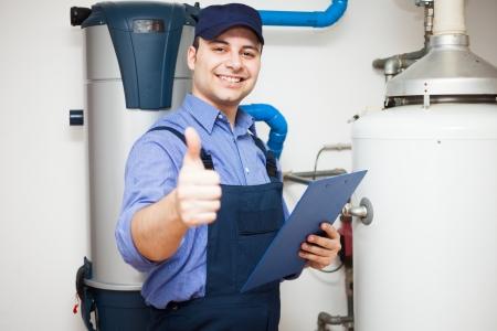 mantenimiento: Sonre�r t�cnico de servicio a un calentador de agua caliente Foto de archivo
