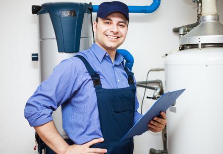servicing: Smiling technician servicing an hot-water heater