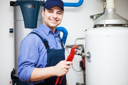 upkeep: Portrait of a smiling plumber at work