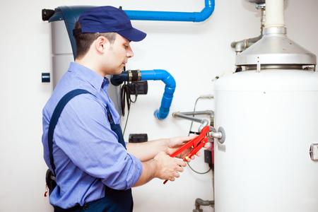 upkeep: Plumber repairing an hot-water heater Stock Photo