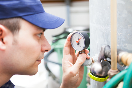 Worker controlling a pressure gauge photo