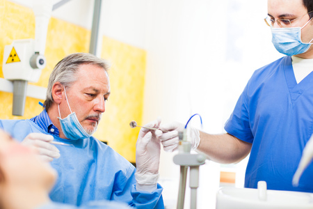 dental clinic: Portrait of a dentist and his assistant at work