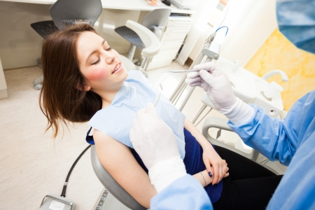 Dentist doing a dental treatment on a female patient photo