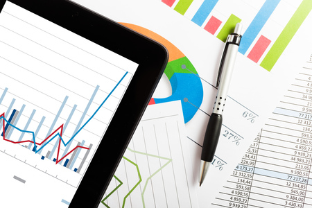 financial paperwork: Tablet computer and financial charts