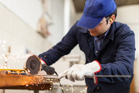 Portrait of a worker grinding a metal plate