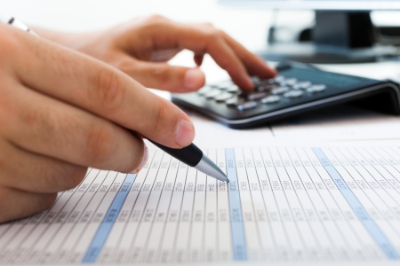 calculator money: Accountant checking numbers on a document