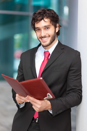 Portrait of a smiling businessman holding a notebook photo