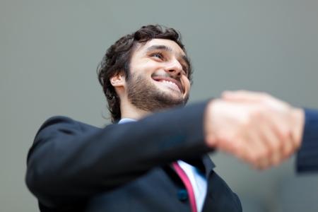 Handsome businessman giving an handshake