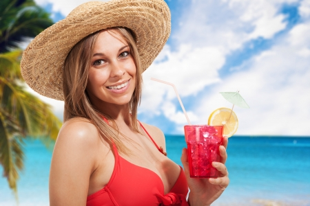 Beautiful woman drinking a cocktail on the beach photo