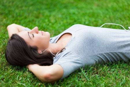 여성 듣는 동안 잔디에 휴식 음악 스톡 콘텐츠