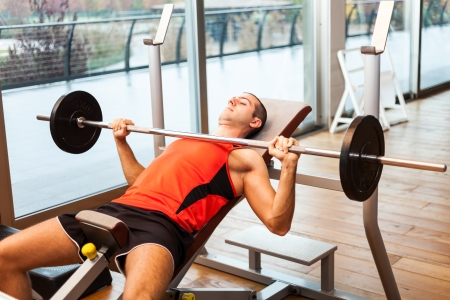 Man lifting a weight in a fitness club Stock Photo - 23530408