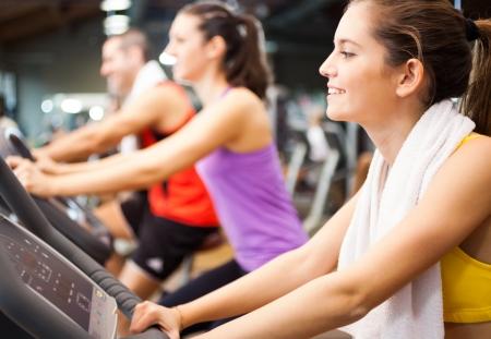 Lachende vrouw doen indoor fietsen in een fitnessclub Stockfoto - 23530936