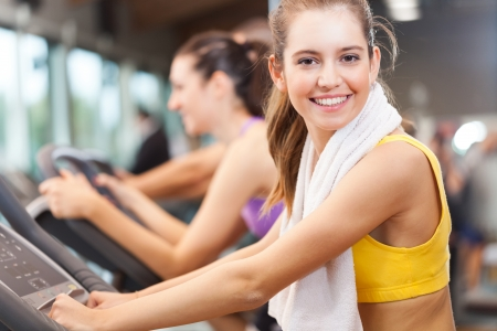 fitness club: Happy people doing indoor biking in a fitness club