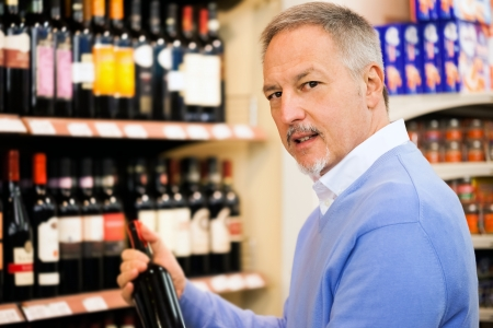 Man in a supermarket choosing a wine bottle photo