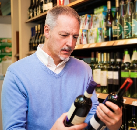 Man choosing the right wine in a supermarket photo