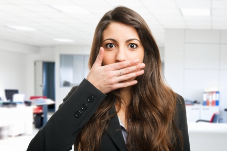 hands in mouth: Woman shutting her mouth Stock Photo