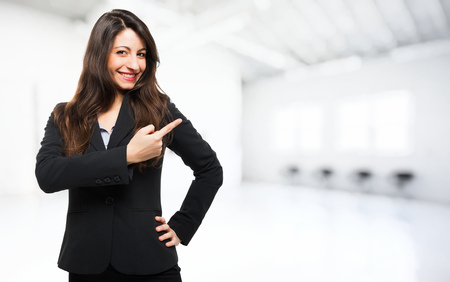 Smiling businesswoman pointing her finger to the copyspace photo