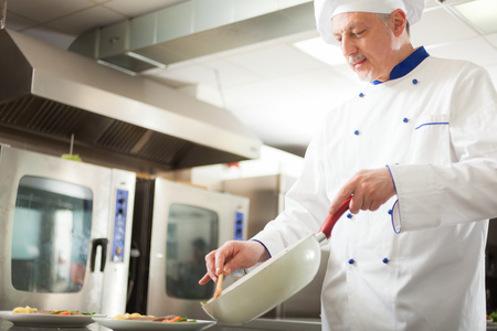 Cocinero que trabaja en su cocina Foto de archivo - 24209605