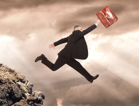 taking a risk: Businessman jumping in a precipice