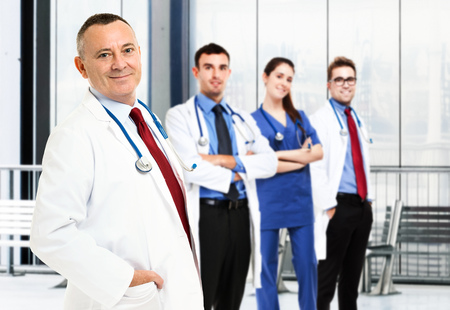Portrait of a smiling doctor in front of his team photo