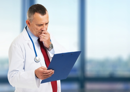 oncologist: Senior doctor reading a case history