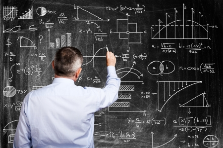 businessperson: Man writing on a blackboard Stock Photo