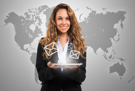 email contact: Woman holding a digital tablet in front of a world map