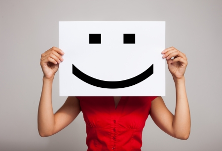 satisfied people: Woman holding a smiling face emoticon Stock Photo